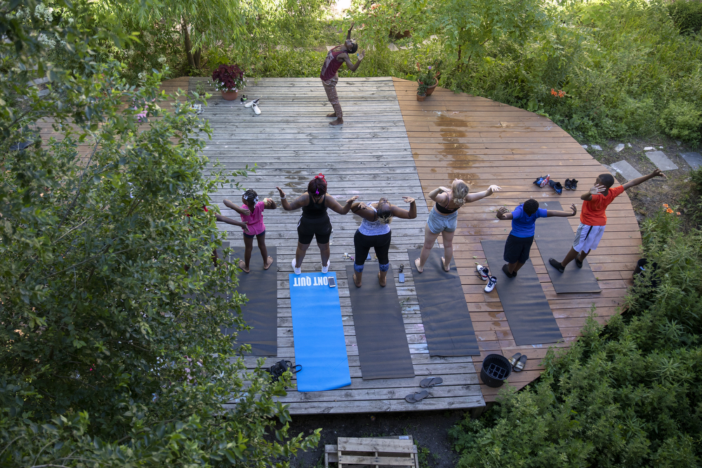 "Indigo Monae leads a yoga class at the Yoga Gardens space Monday, July 2, 2018, in the Lawndale neighborhood of Chicago. Monae is yoga teacher who saw a need for a safe and peaceful community space while she was living in a building next to an empty lot in Lawndale. Over the past 8 years, with help from other volunteers in the yoga community and funds from classes taught at Montrose Beach, Monae transformed the empty lot into a lush garden with a deck for yoga practice, drawing in young and old from the neighborhood. While living in Lawndale, she found access to healthy food options troublesome, and after witnessing young people involved in violence and drug dealing outside their home, she and her friends decided, ""First of all, we need food, we need to teach them yoga, we need something to make them feel at peace,"" she said. ""So that's how it began, just some yogis wanting to share some love."" (Erin Hooley/Chicago Tribune)"
