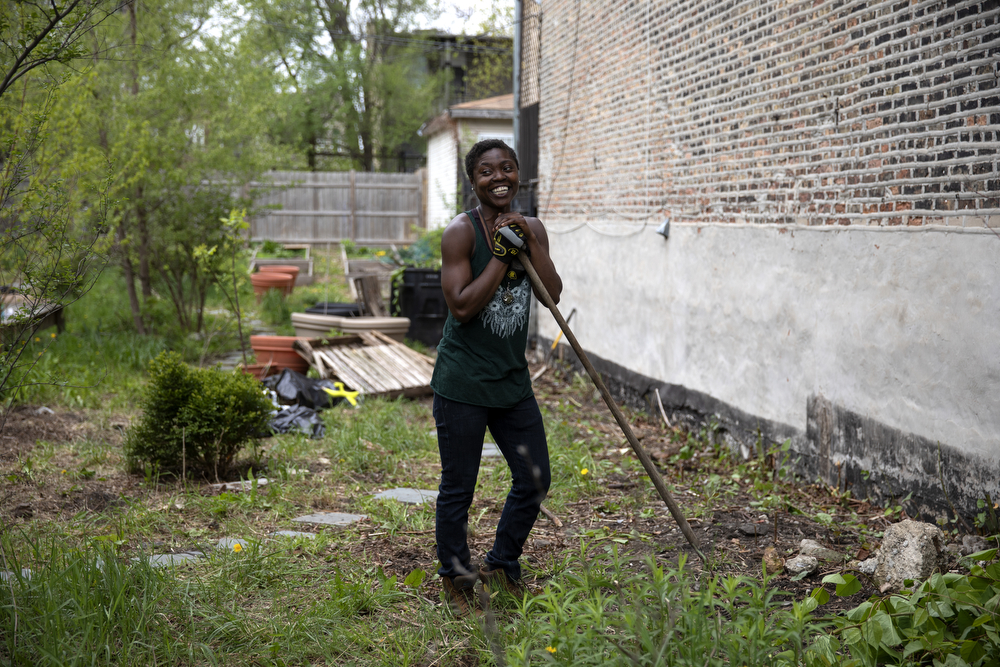 "Indigo Monae works in the Yoga Gardens space Sunday, May 13, 2018, in the Lawndale neighborhood of Chicago. Monae is yoga teacher who saw a need for a safe and peaceful community space while she was living in a building next to an empty lot in Lawndale. At first, the space was an empty field covered with rubbish without much vegetation. One morning while she was meditating on her porch, she said, ""I saw this 10-year-old boy with a huge line of older people, like, down the alley. I was like, 'What's going on? What's going on?' And then I realized he was selling drugs to all these grown people. I was like, 'Whoa!' And it wasn't regular drugs, it was like heroin and things."" Over the past 8 years, with help from other volunteers in the yoga community and funds from classes taught at Montrose Beach, Monae transformed the empty lot into a lush garden with a deck for yoga practice. (Erin Hooley/Chicago Tribune)"