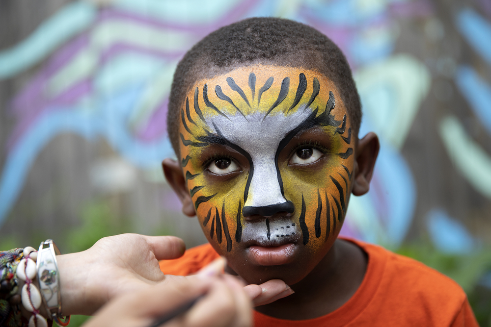 "Volunteer Trina Gerardi paints the face of Camaijah Duff, 6, during a community gathering event at the Yoga Gardens space Thursday, June 28, 2018, in the Lawndale neighborhood of Chicago. Indigo Monae said she wanted to have an informal opening of the season for the gardens, because the space is not open every day and is closed during the winter. ""So, the barbecue was a way to show the community like, 'Hey, we're here, we're still here, we're open, come in. This is for you.' And they enjoyed it. They loved it,"" she said. (Erin Hooley/Chicago Tribune)"
