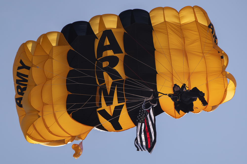 A member of the U.S. Army Parachute Team Golden Knights carries a Red Line flag, representing the sacrifices of firefighters and first responders, as he descends during the Chicago Air and Water Show at North Avenue Beach Sunday, Aug. 19, 2018, in Chicago. The flag was presented to Chicago Fire Department Deputy District Chief Ron Dorneker and members of the fire department Special Operations SCUBA team in honor of Juan Bucio, who lost his life while attempting a dive rescue in May, and all of Chicago's fallen firefighters and first responders. (Erin Hooley/Chicago Tribune)