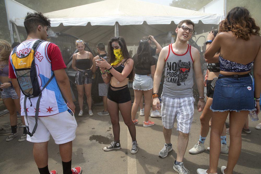 Festival goers stand in front of large fans on a hot day four of Lollapalooza Sunday, August 5, 2018, at Grant Park in Chicago. (Erin Hooley/Chicago Tribune)