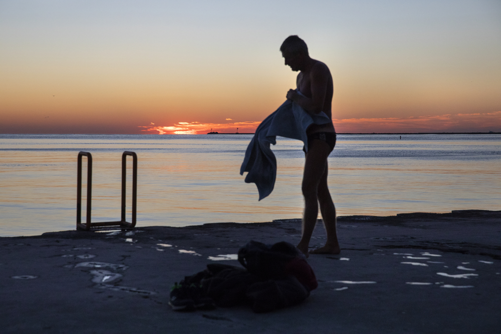 "Ihor Hulovatyy towels off after a chilly dip in Lake Michigan as the sun rises near Oak Street Beach Tuesday, Oct. 16, 2018, in Chicago. Hulovatyy said he uses the water to ""wake up"" each morning, except if the waves are too high or there is snow and ice. (Erin Hooley/Chicago Tribune)"