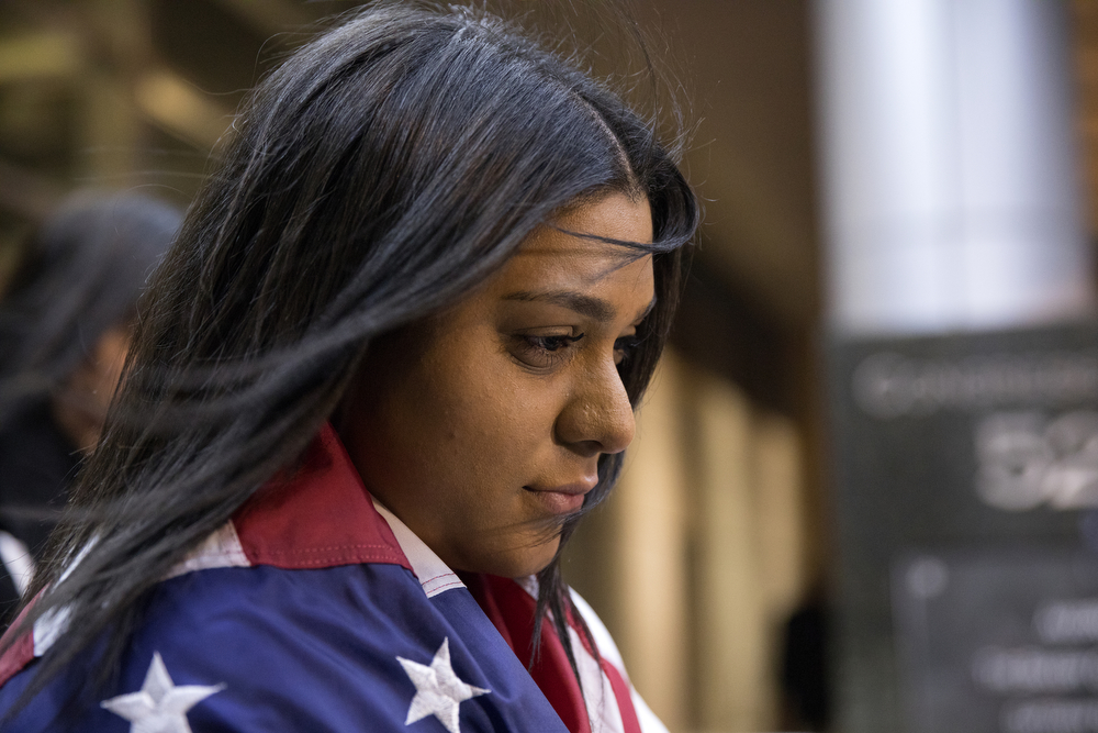17-year-old Maryori Urbina-Contreras is wrapped in an American flag as she stands with friends and family after being granted asylum by a judge at Chicago Immigration Court Wednesday, Feb. 28, 2018, in Chicago. Maryori is one of 68,000 unaccompanied children who flooded across the southwest border of the United States, causing a humanitarian crisis in 2014. Fleeing gang violence in her home country of Honduras, Maryori travelled alone over 1,500 miles for several weeks in 2014 before reuniting with her mother Tania Contreras, who has been in the United States since 2001. In 2015, an immigration court judge postponed a final hearing for Maryori until today, when a Chicago Immigration Court judge granted her asylum. (Erin Hooley/Chicago Tribune)