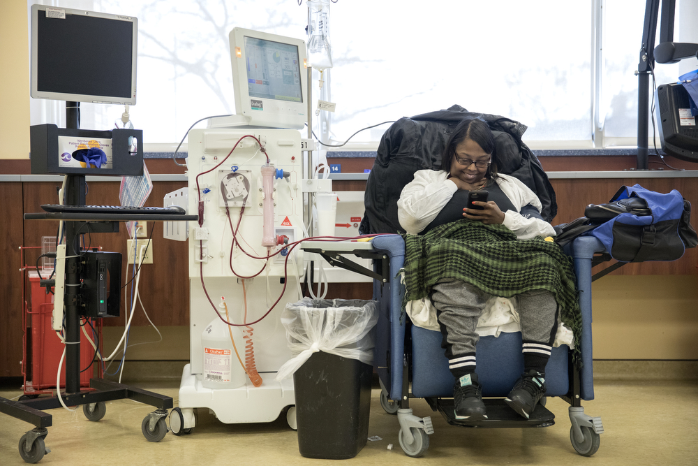 Melanie Perry looks at her phone as she undergoes her tri-weekly dialysis treatment, removing toxins from her blood, at DaVita Woodlawn Dialysis clinic Thursday, April 5, 2018, in Chicago. As a child, Perry developed Lupus, resulting in damage to her kidneys. After doctors recently said her eligibility for a transplant is running out due to complicated health issues, Perry created a Facebook post asking people to contact her transplant team if they are able and willing to donate a kidney, otherwise she may be on dialysis for the rest of her life. Erin Hooley/Chicago Tribune)