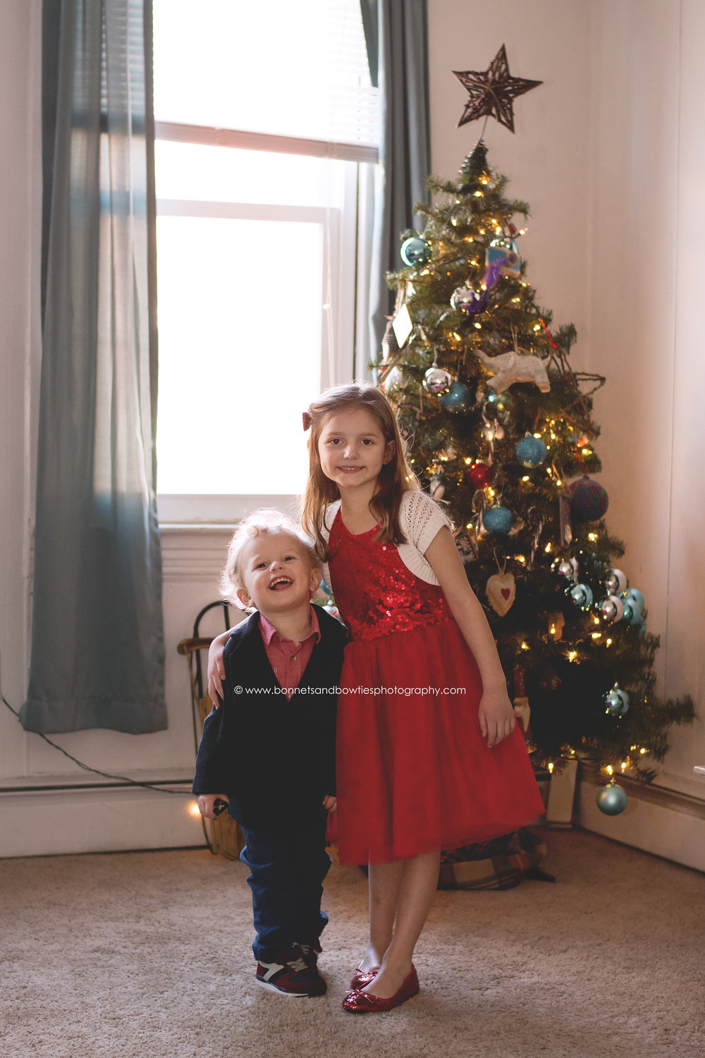 girl and boy by christmas tree.jpg