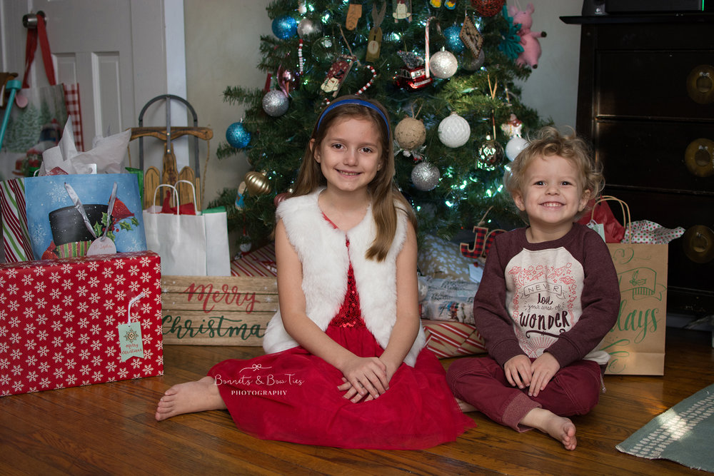 girl and boy onchristmas day in front of tree.jpg