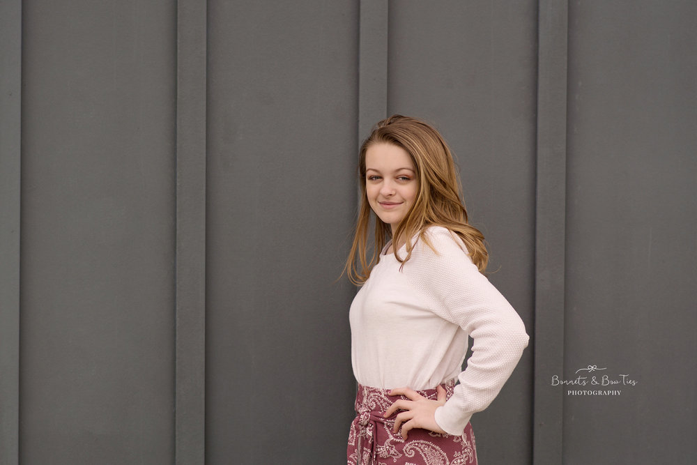 girl posing against grey wall.jpg