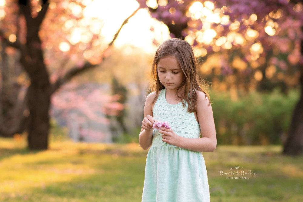 girl posing holding flower petals.jpg