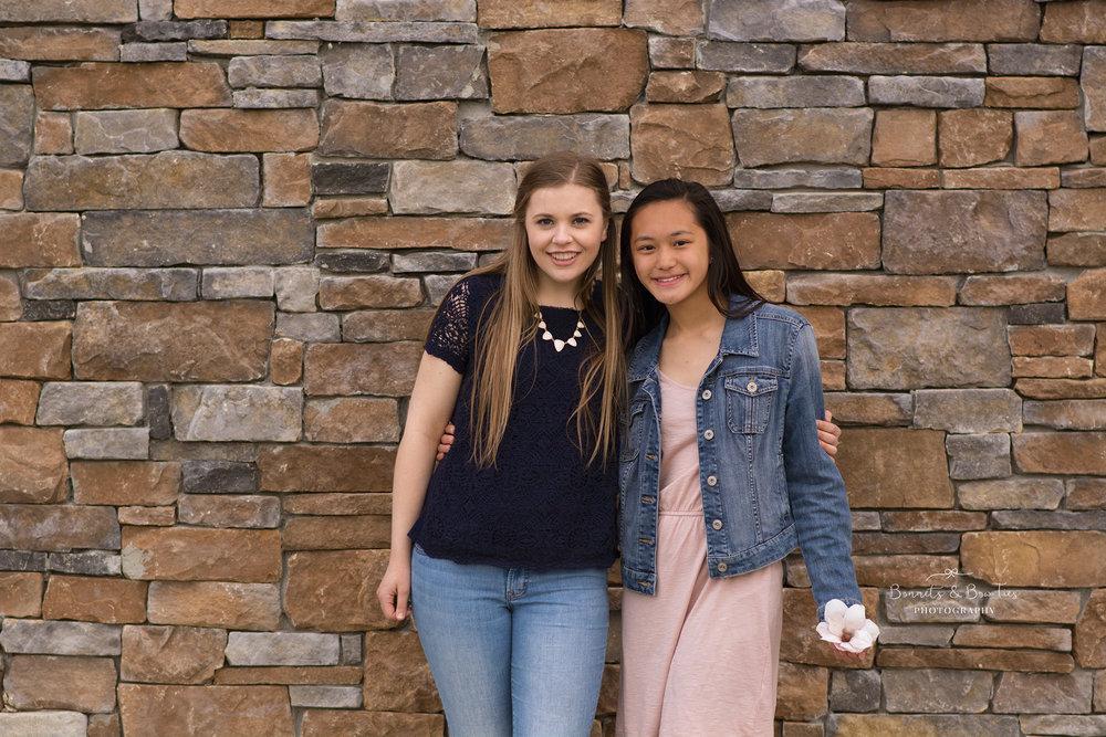 teen girls posing against rock wall.jpg
