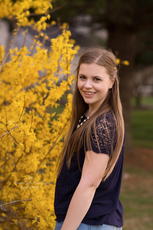 girl posing near yellow flowers.jpg