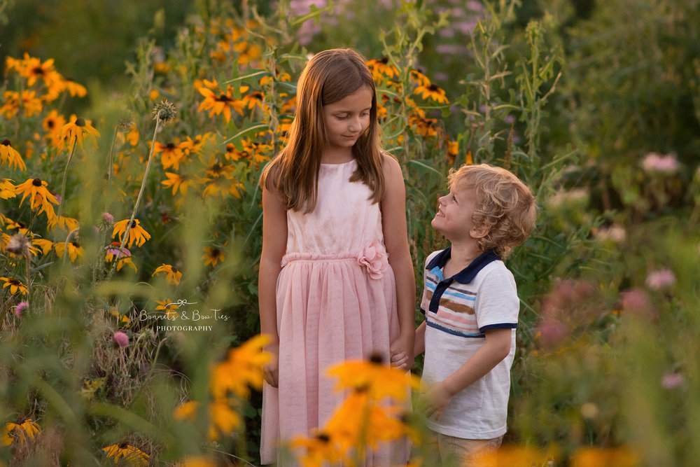 two kids standing in a flower field.jpg