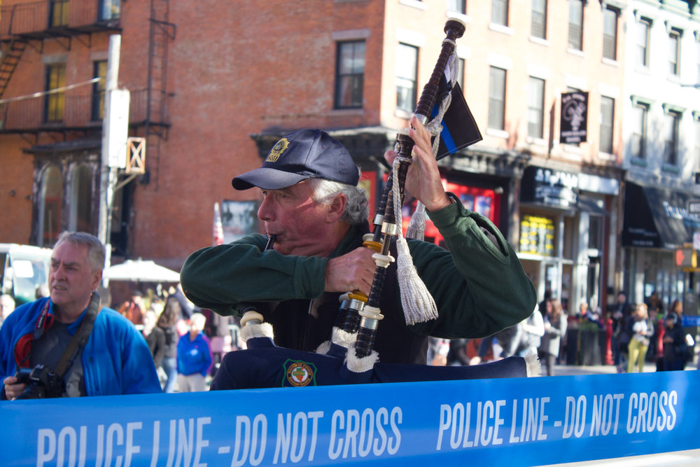 A man plays the bagpipes for marathoners and spectators alike in Brooklyn.