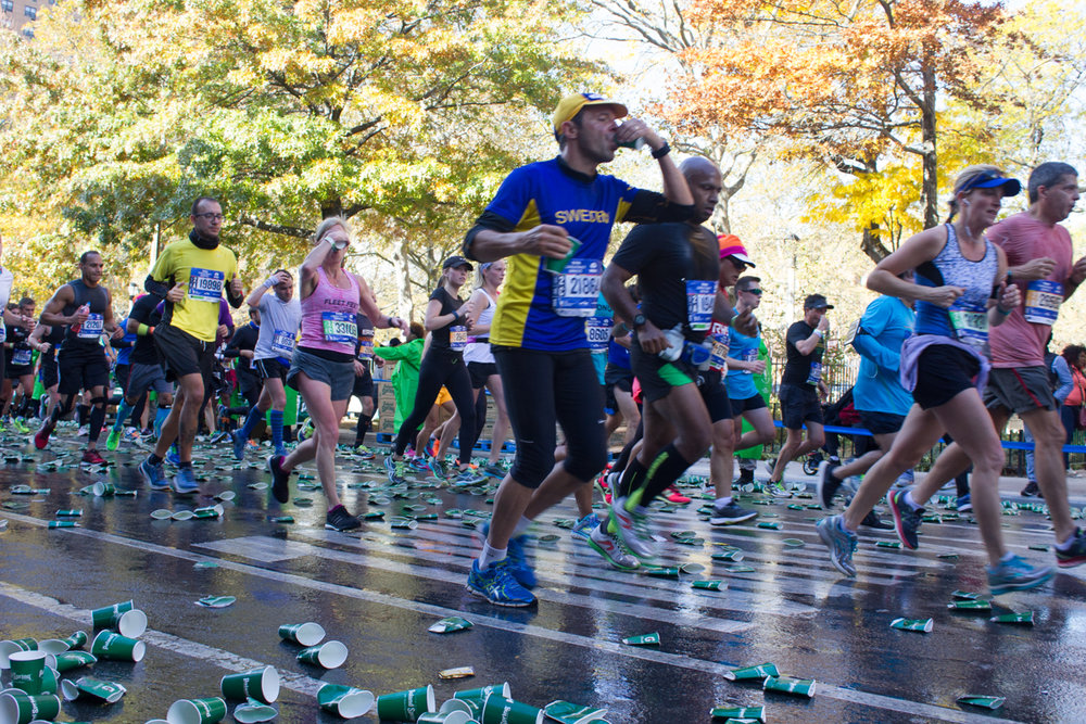 Runners drinking beverages on the go throw their finished cups to the floor.