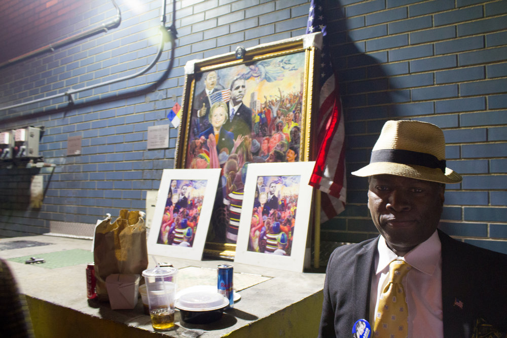 A man sells artwork depicting Martin Luther King Jr. and Obama standing behind Hillary Clinton to people standing in line for Clinton's event.