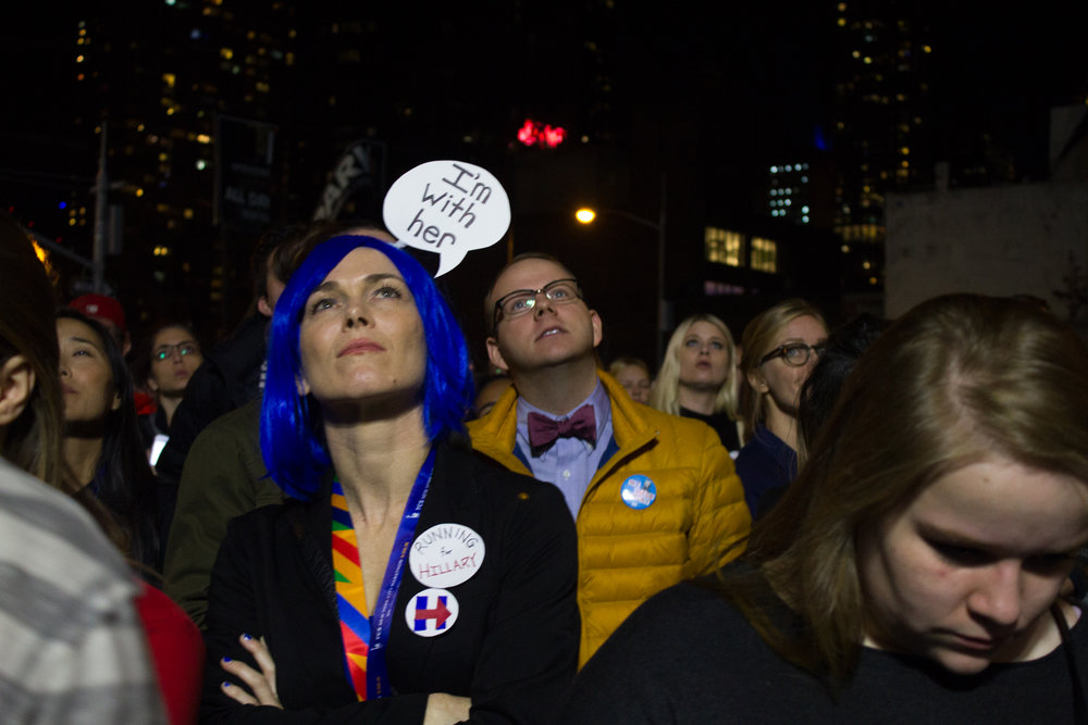 Niki Rarig, 34, looks on as poll results come in at the Javits Center. Rarig and a friend dressed up as the Clinton logo for Halloween (both wore all blue and carried a red arrow between them), and she decided that election night was a fitting time for a reprise.