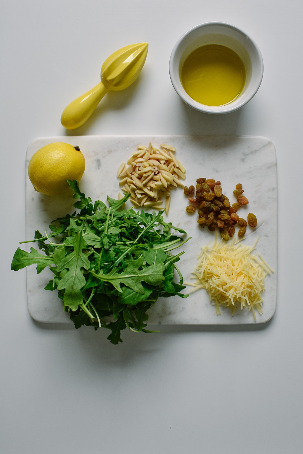 Arugula salad with golden raisins, almonds, and parmesan cheese