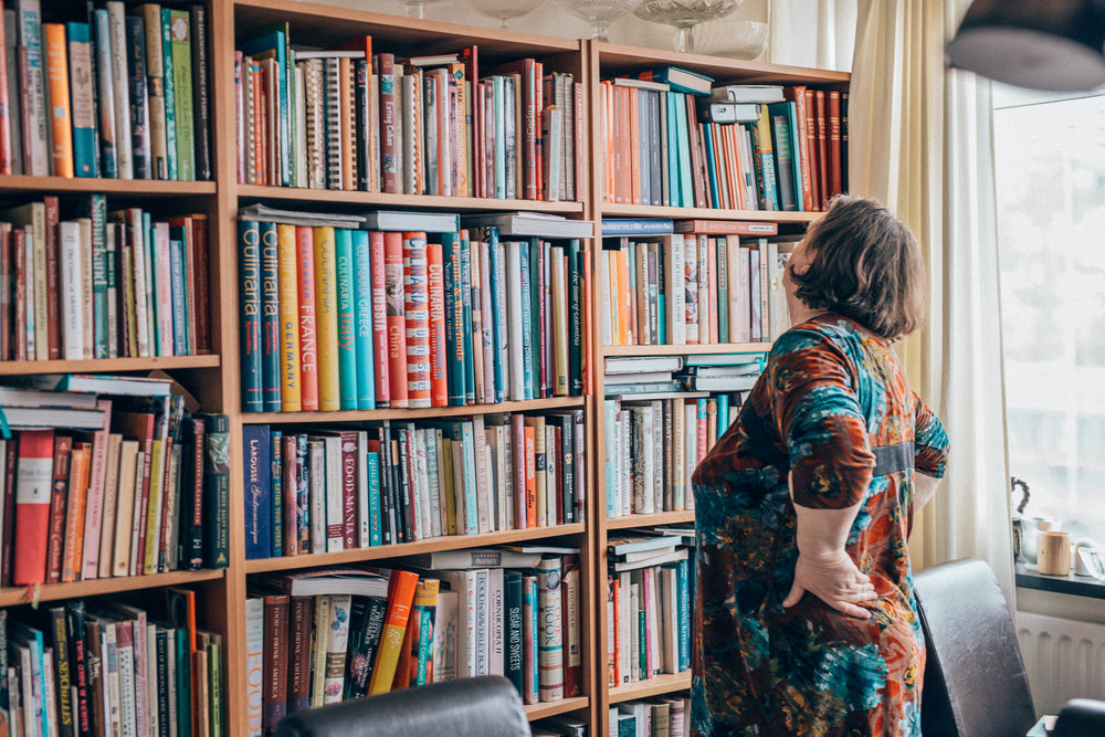 Photo by The Curated Feast of Nanna in her library, looking for a book