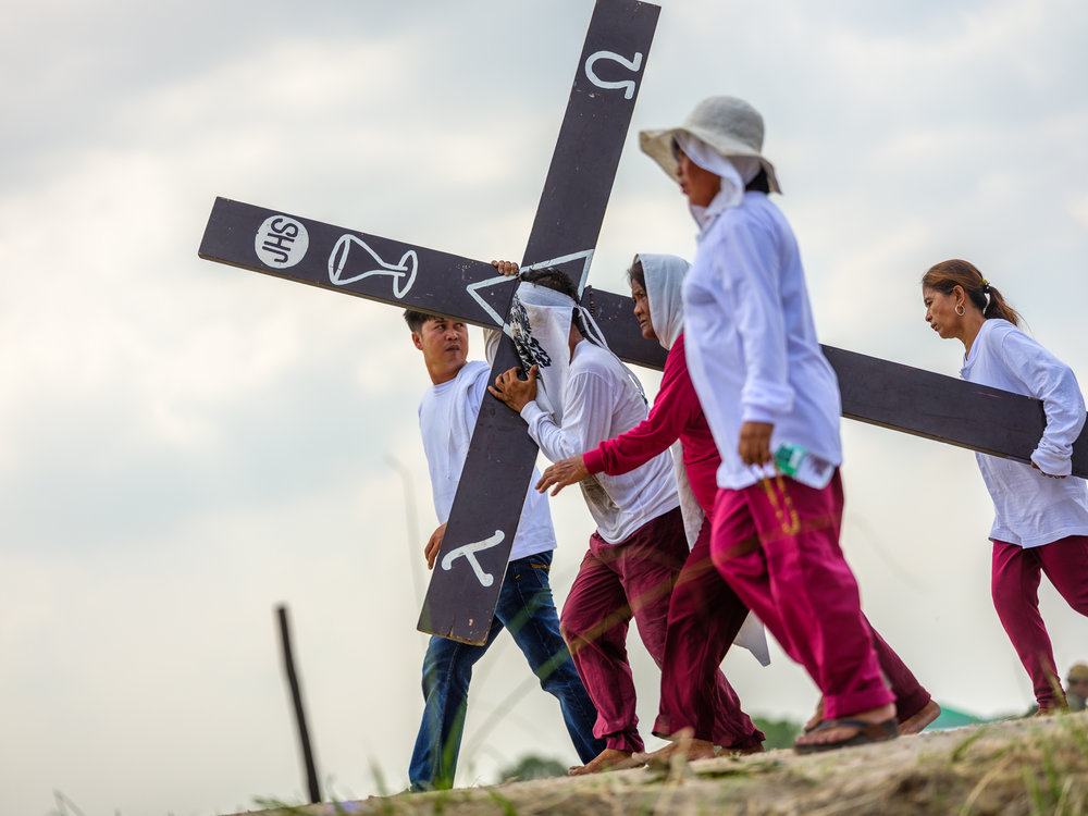 Devotee penitents carry heavy wooden crosses for several kilometres up to the crucifixion site atop a hill outside san pedro cutud, pampanga.  Fuji GFX, 110mm.