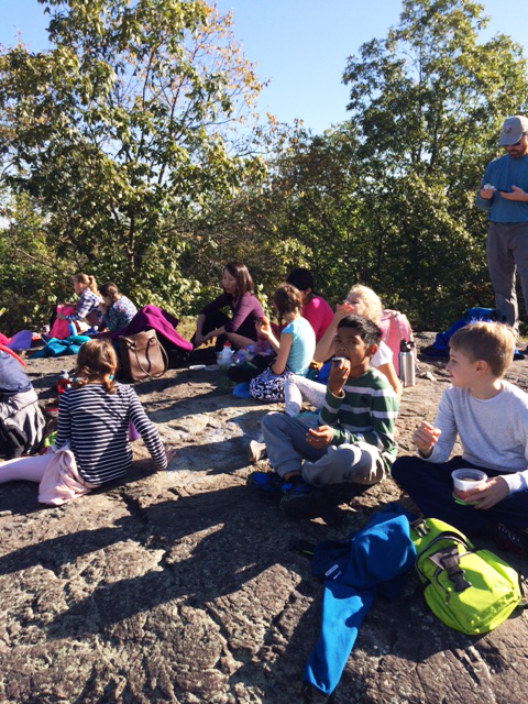 "After a quick stop at Locke Pond, the students finally climbed Whipple Hill from the east and happily settled down for a well-deserved snack once they reached the ""summit""."