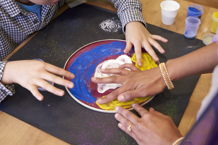 Grade 4 students using a stencil to create Rangoli with colored rice flour