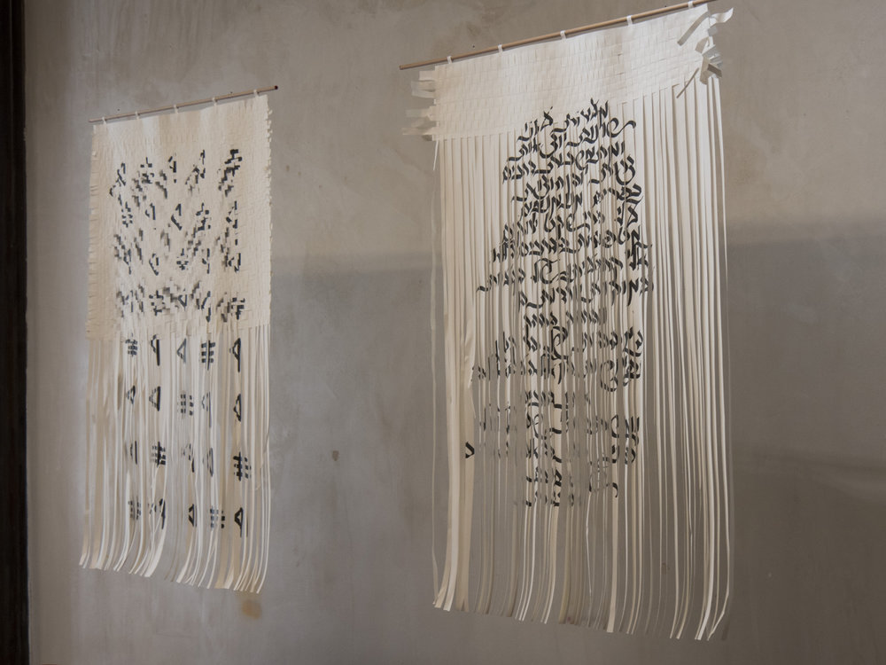 "left:  ORDER | Ink on woven paper, 70x100 cm  Translation to ancient Hebrew script  *Source language: Hebrew   Right:  At the Station | Ink on woven paper, 70x100 cm  First paragraph of ""At the Depot"" (1906) by Dovid Bergelson translated to Hebrew  *Source language: Yiddish"
