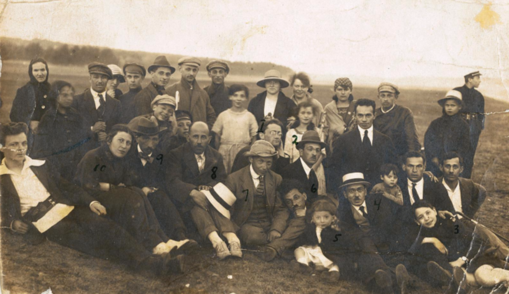 Dovid Bergelson (6, on ground with his head on his neighbour's knee), his wife Zipora (10, seated, second from left), and only son - Prof. Lev Bergelson (5, small child to Bergelson's left) among a group of friends and colleagues.