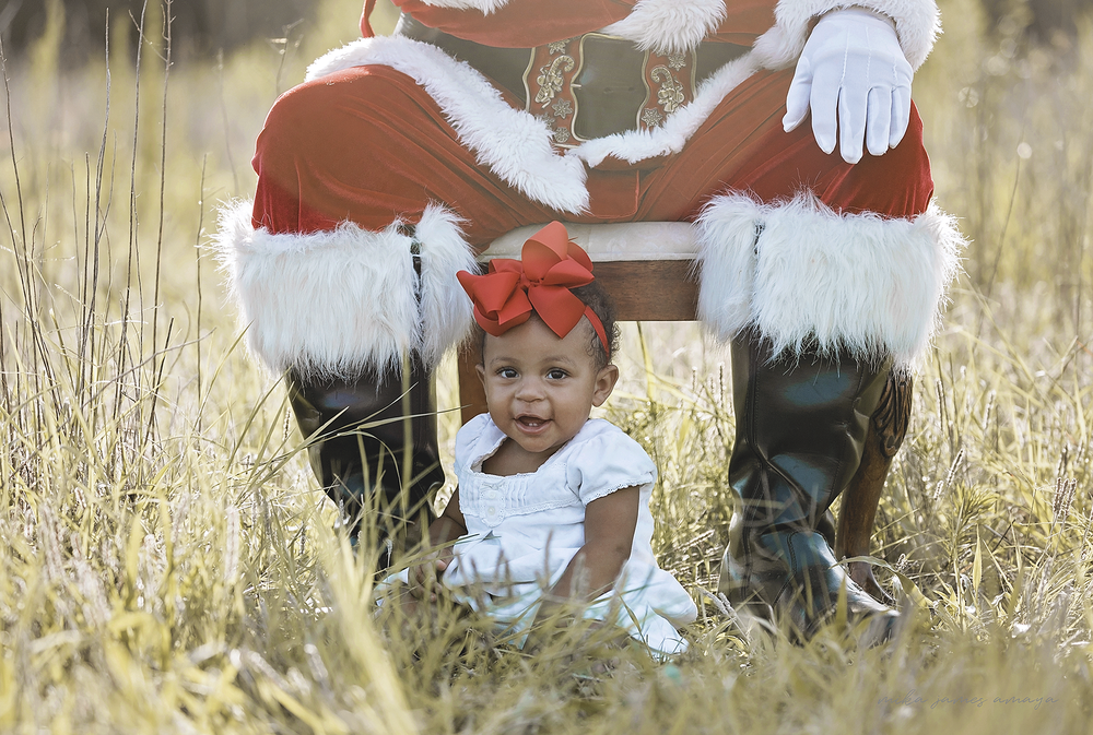 cute baby girl with big red bow in a white dress posing with Santa in a field
