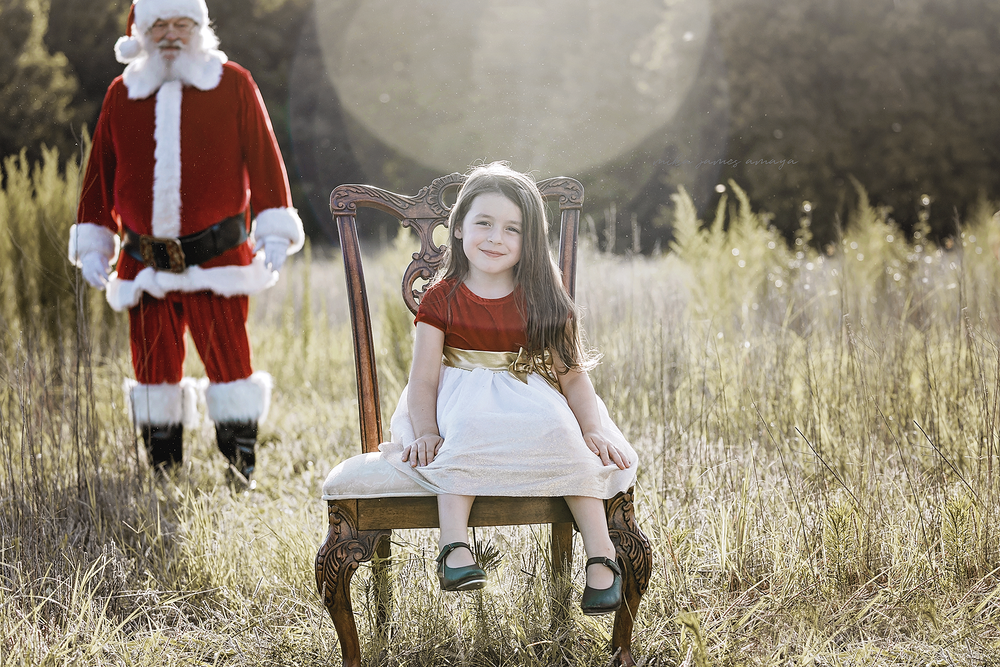 cute little girl sitting in a chair in a field Santa is coming from behind