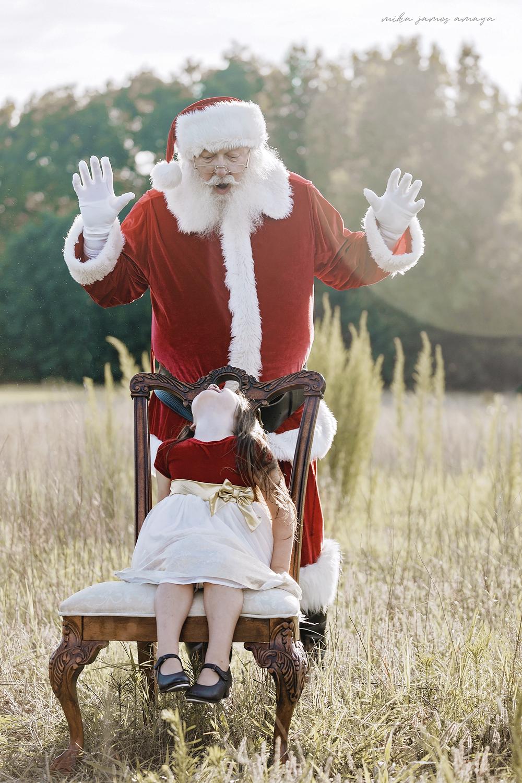 Santa surprises cute little girl sitting in a chair in a field