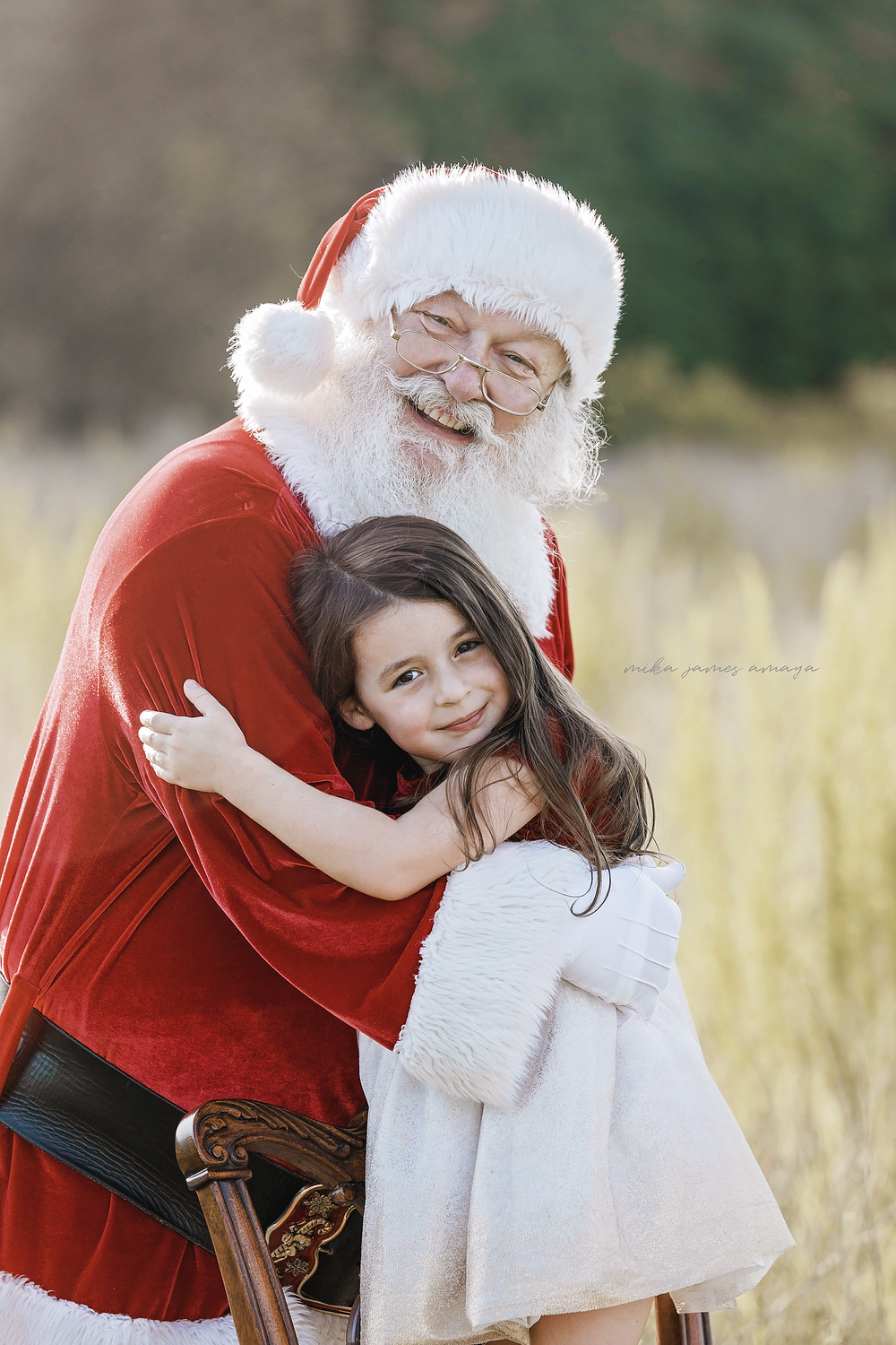Santa hugs cute little girl while she stands on a chair in a field