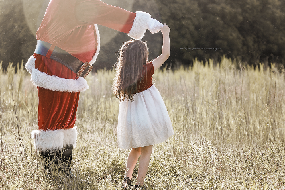 Santa dancing with a little girl in a field