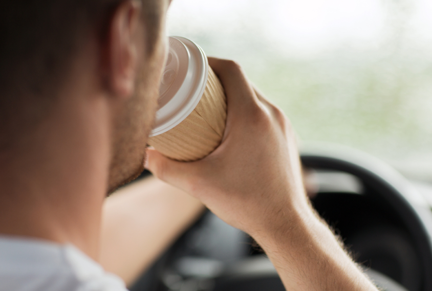 man drinking coffee while driving the car.jpg