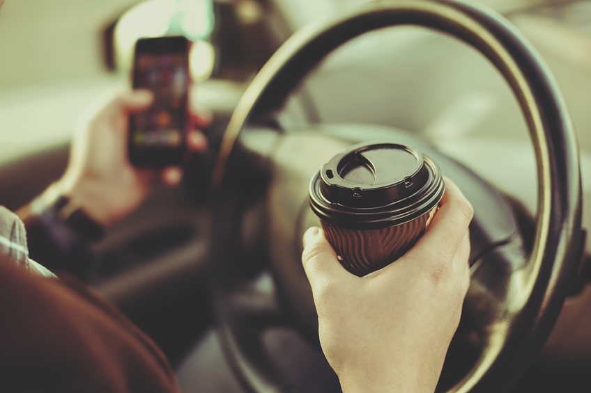 A driver checks their mobile phone while holding a coffee