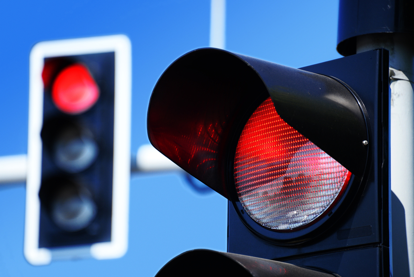 Traffic lights against blue sky showing red signal