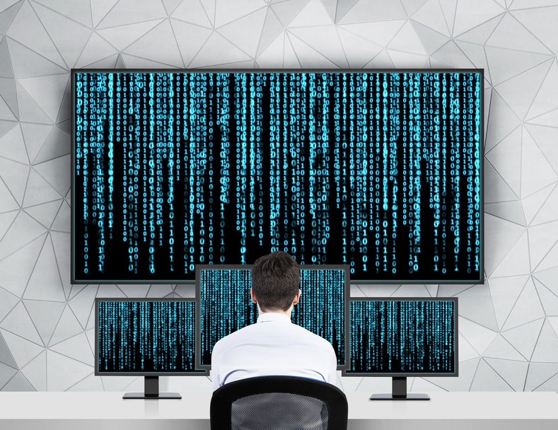 A businessman looking at multiple computer screens of software