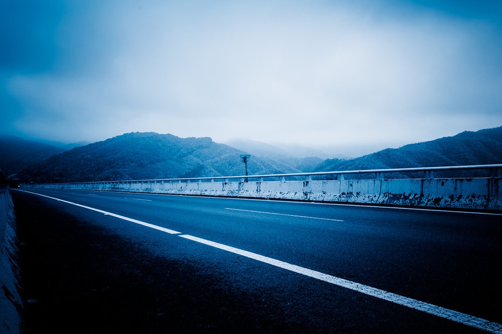 Empty road in mountains surrounded by cloud
