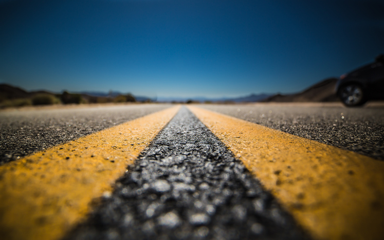 Close-up image of dual yellow lines on road surface against blue sky