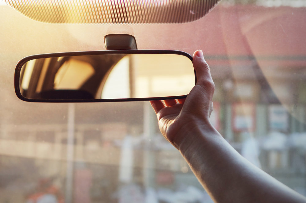 Hand adjusting the rear view mirror in a car