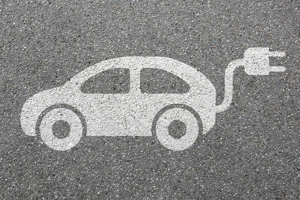 Electric car charging symbol in white paint on tarmac