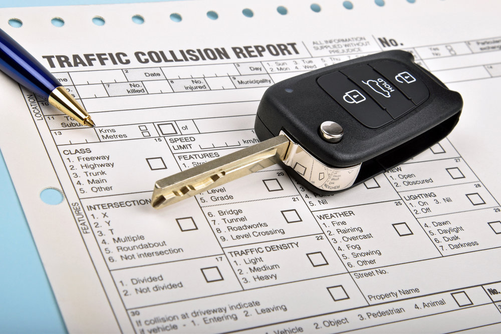 Car key on top of a traffic collision report form