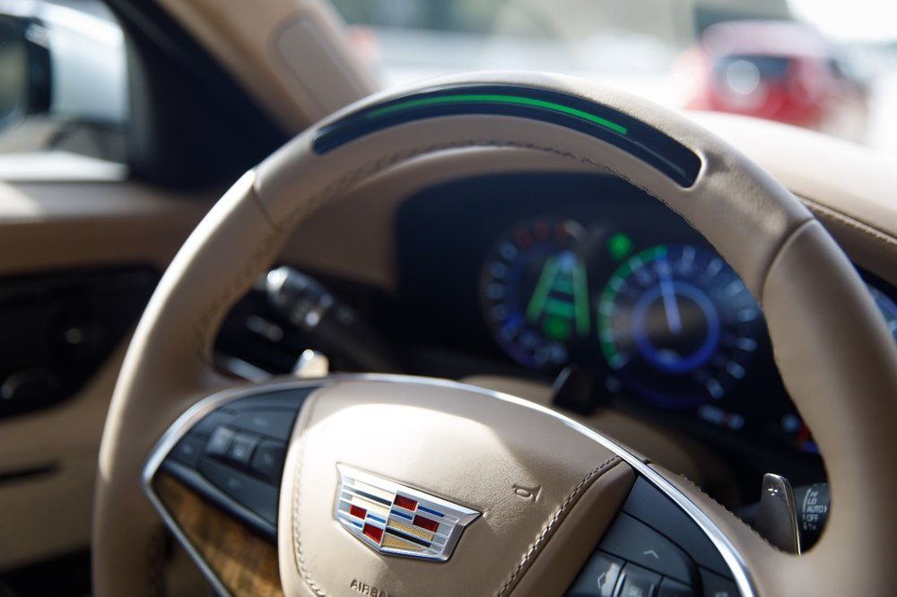 A steering wheel light bar indicates the status of Super Cruise and will prompt the driver to return their attention to the road ahead if the system detects driver attention has turned away from the road too long. [image courtesy of cadillac]