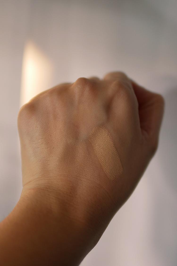 Tampilan Concealer SPF 25 warna Almond pada wajah di foto atas, dan tampilan Concealer SPF 25 warna Almondyang sudah dibaurkan pada sebelah kiri dan yang belum dibaurkan pada sebelah kanan punggung tangan.