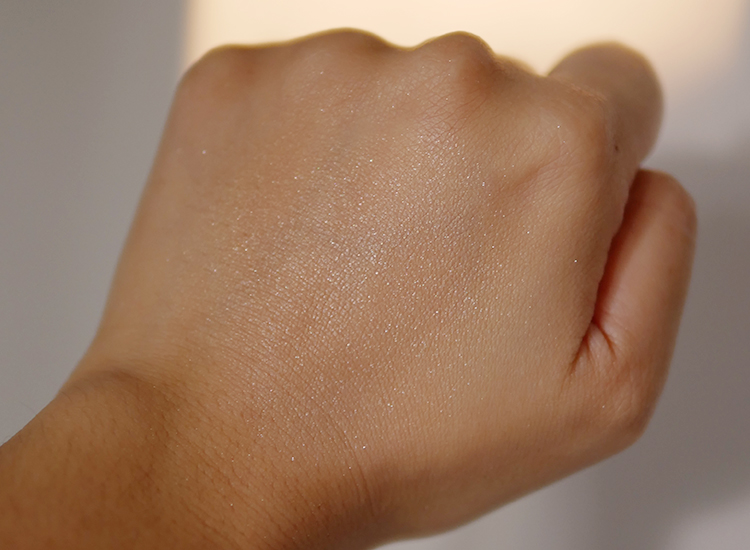Wajah dan  swatch  pada punggung tangan menggunakan LUMINIZING FACE ENHANCER warna No.16/Almond.