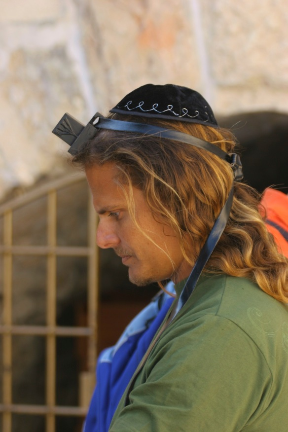 Using a tefillin to communicate with the Almighty for better reception. Jerusalem, Israel.