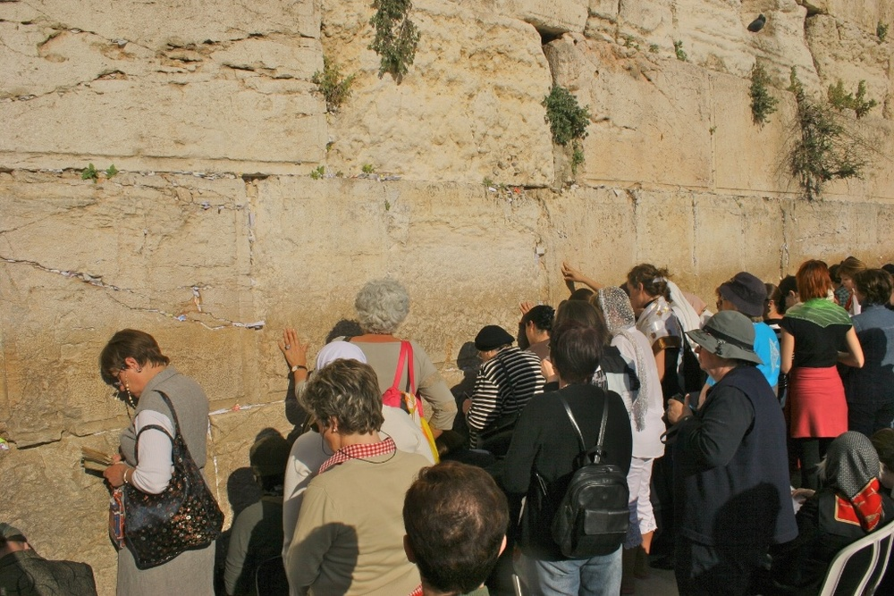 Worshippers inserting prayers on paper in the Wailing Wall. Jerusalem, Israel