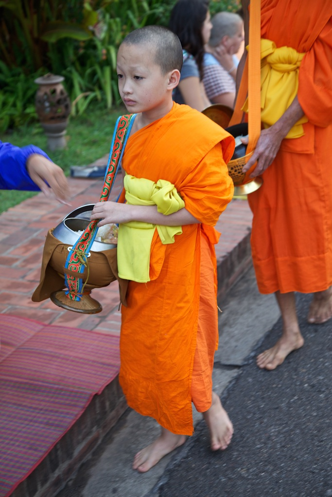 Monk in training with bowl for rice alms. Luang Prabang, Laos.