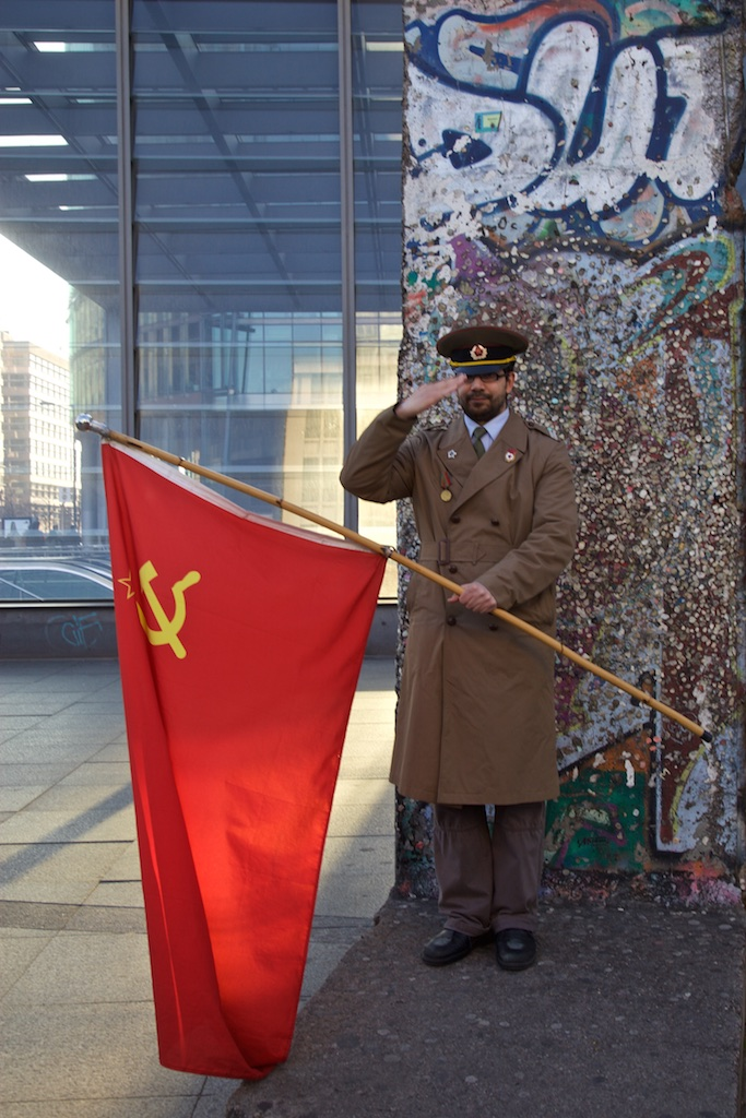 A survivor of the defunct Soviet Union standing by a remnant of the Berlin cold war wall. Berlin, Germany.