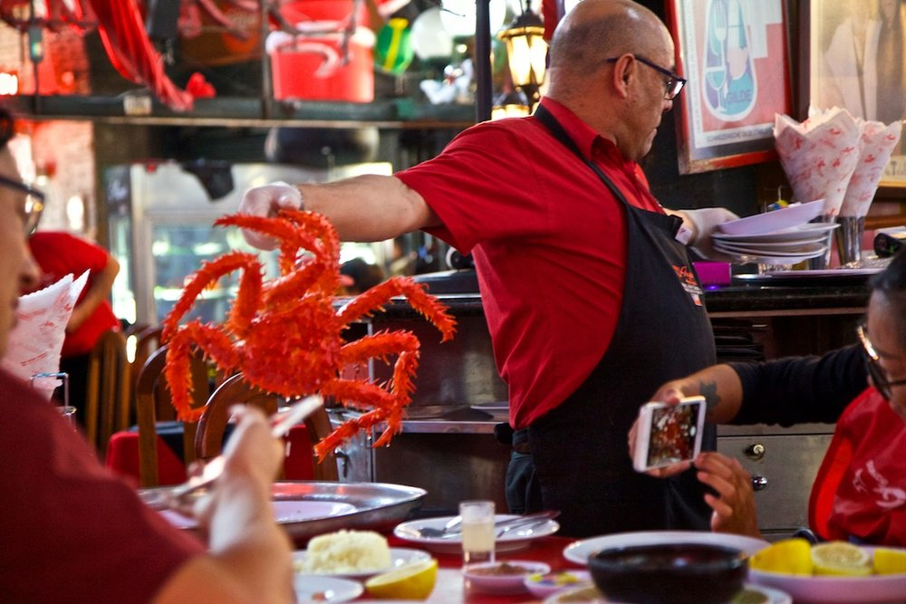 - Professionals at Work: During the limited season to devour the centolla crab, a waiter expertly serves one to a waiting customer. Santiago de Chile.