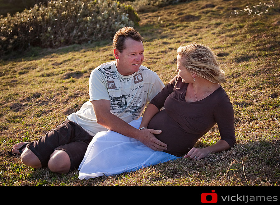 pregnant lady and man lying on hillside