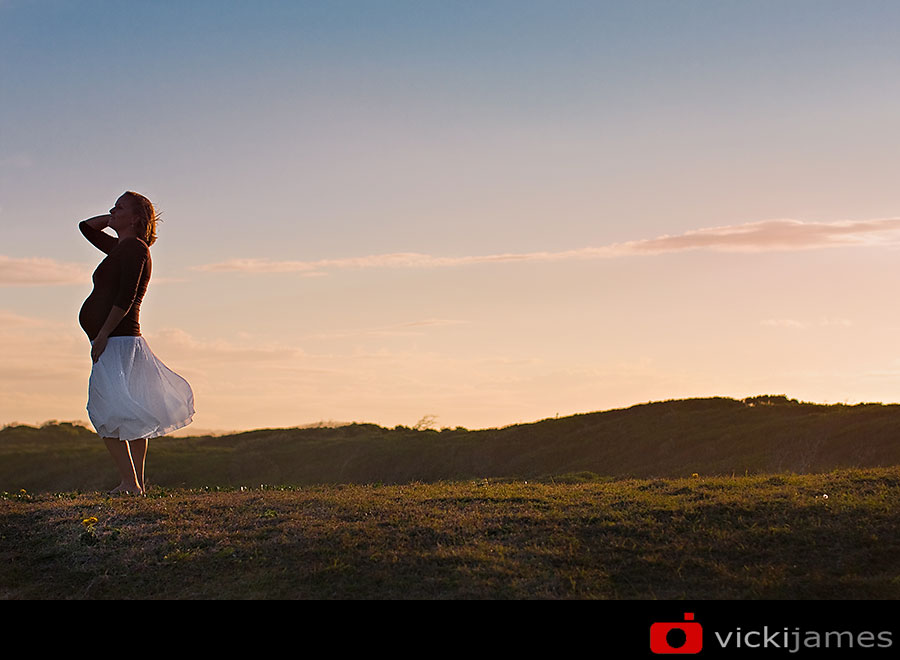 pregnant lady silhouetted against sky at sunset